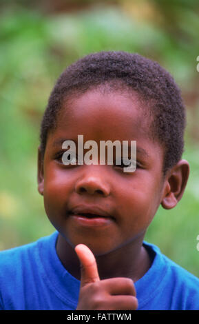 Young African boy holding the thumbs up happy and positive sign in the Seychelles Islands - Stock Image