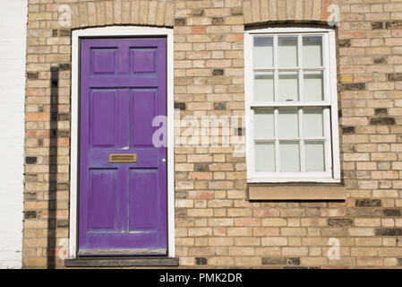 Violet pastel vintage front door on a restored brick wall of a Georgian house residential building with white wooden sash window - Stock Image