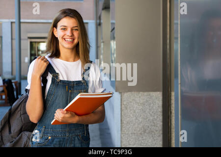 Portrait of a happy teen student girl at the entrance of the school - Stock Image