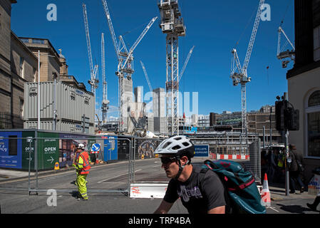 Cyclist passes the redevelopment of the St James Centre at the East End of Princes Street, Edinburgh, Scotland, UK. - Stock Image