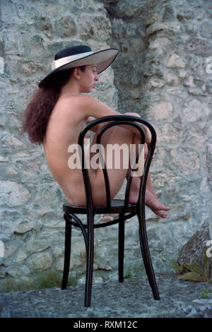 young woman with long hair sits naked on a chair sunbathing in a garden hungary 1980s - Stock Image