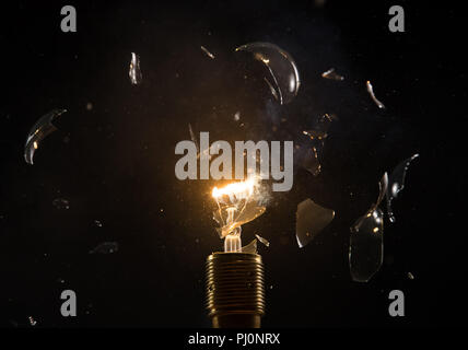 Freeze motion of old light bulb explosion on black backround. Concept of new idea and brain storming. - Stock Image