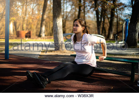 Beautiful woman doing sport on outdoor park during fall and sunset - triceps exercise - Stock Image