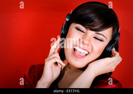 Stock image of woman wearing headphones, Listening to music and singing over red background - Stock Image