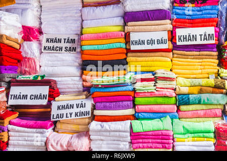 towels in many colors, sizes and types, on the market stall in Hanoi, Vietnam, stacked in pile, descriptions in vietnamese. - Stock Image
