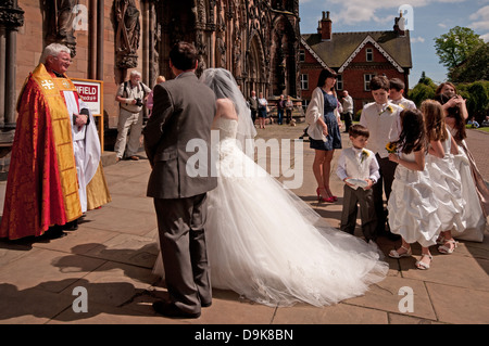 Bridal party with Bride in white wedding dress meeting Canon Wealands Bell at west front of Lichfield Cathedral - Stock Image