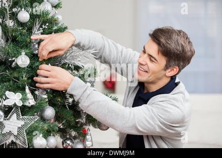 Man Decorating Christmas Tree At Home - Stock Image