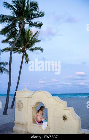 Hollywood Florida Hollywood Beach Boardwalk Atlantic Ocean palm tree public beach ocean wall woman bikini sitting drying dusk sa - Stock Image