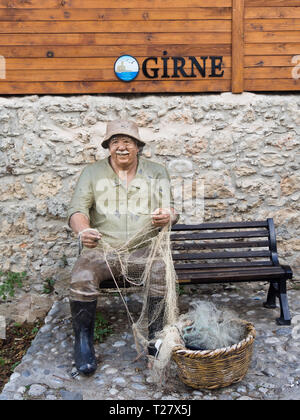 Fun sculpture of a local fisherman placed in a popular tourist pedestrian passage in Kyrenia ( Girne ) in northern Cyprus - Stock Image