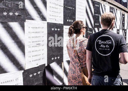Couple photographed from behind walking on a street in Brixton next to a wall covered in black and white posters. Brixton, Lambeth, South London, UK - Stock Image