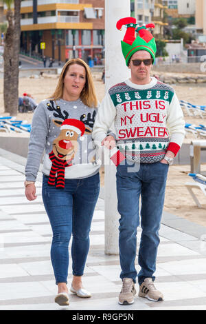 Benidorm, Costa Blanca, Spain, 25th December 2018. British tourists dress for the occasion on Christmas Day in this favourite getaway destination for Brits escaping the cold weather at home. Temperatures will be in the mid to high 20's Celsius today in this mediterranean hotspot. Young man and  woman wearing Christmas jumpers strolling onn the promenade sea front. - Stock Image