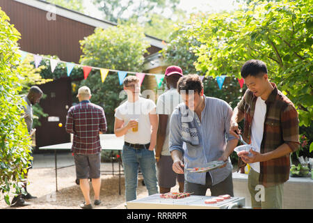 Male friends enjoying barbecue in sunny backyard - Stock Image