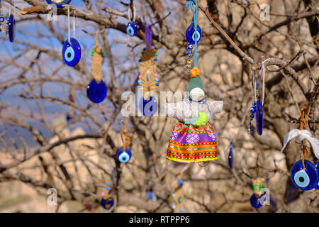 Public tree decorated with Evil Eye and doll pendants on a Cappadocia road side.  Blurry background of local rock formation - Stock Image