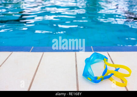 Swimming Goggles on the edge of a swimming pool. - Stock Image