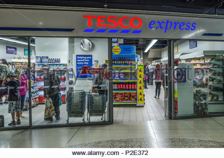 Entrance to retail chain store with shoppers: Tesco express shops are neighbourhood convenience stores averaging 200 square metres.  Because the store - Stock Image