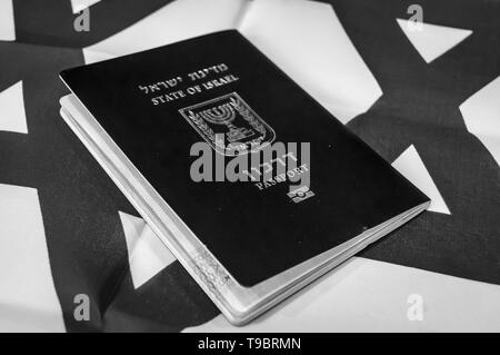 A blue passport of the State of Israel on Israeli flag on the background. Israel citizenship concept, Israeli biometric 'darkon' passport illustrative - Stock Image