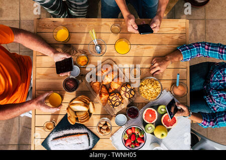 Breakfast time in vertical top view with family of friends eating together - technology mobile internet social network addiction for caucasian people - Stock Image