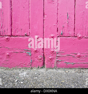 Close up of the base of a pink door - Stock Image