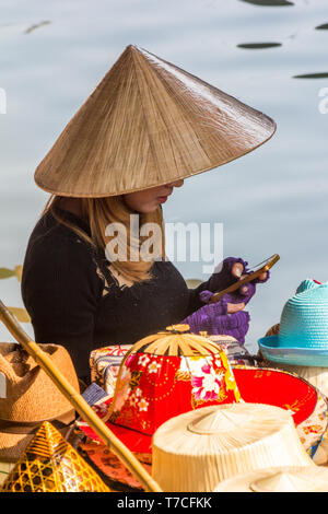 Damnoen Saduak, Thailand - 4th March 2017: Hat vendor on mobile phone.  The floating market is a popular tourist atrraction - Stock Image