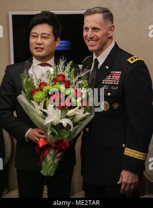 U.S Army Lt. Gen. Thomas S. Vandal commander of the Eighth army, presents flowers to Seo, Jung-Hak after the Holiday concert in Seoul, Korea Dec. 17, 2017. The concert was hosted by the Eighth Army command in conjunction with local community leaders during the holiday season to promote harmonious relations between the U.S. Army and the Republic of Korea (ROK). Over 1500 U.S. Soldiers and ROK soldiers attended performances by the Eighth Army Band and the Prime Philharmonic Orchestra . (U.S. Army photo by Pfc. Edward Randolph) - Stock Image
