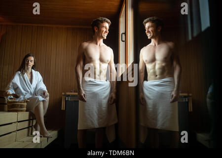 Happy couple enjoying the sauna together at the spa - Stock Image