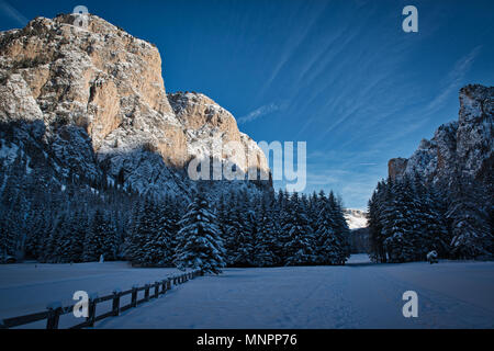 Winter panorama in the valley with sunny mountains on the left and forest in the shadow, Dolomites - Stock Image