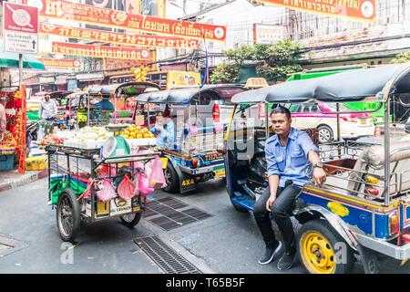 Bangkok, Thailand - January 31st 2019: Tuk tuk drivers on Yaowarat road waiting for business. Chinatown is teeming with the vehicles. - Stock Image