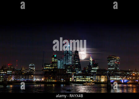 A very large moon rises from behind the towers of the City of London in an unusual display - Stock Image