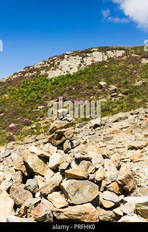 Roughly built cairn amid a patch of loose rocks next to  a footpath on the south western approach to Cat Bells (451 metres) near Keswick, Cumbria. - Stock Image