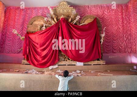 Child watching pandal with Durga statue hidden before start of Durga puja celebration in Kolkata, India - Stock Image