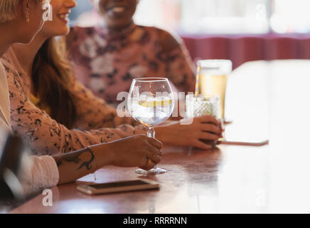 Young women friends drinking cocktails in bar - Stock Image