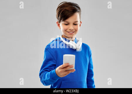 smiling boy in blue hoodie using smartphone - Stock Image