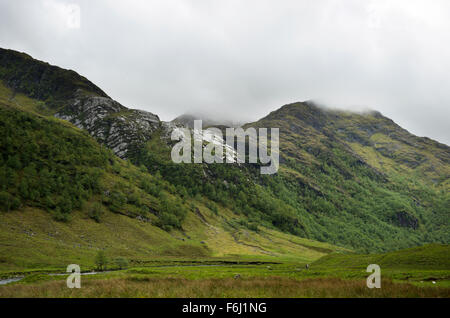 Looking down Glen Nevis on a typically scottish cold and misty day where the tops of the surrounding mountains are - Stock Image