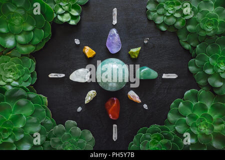 Crystal Grid with Aeonium Frame on Black Table. Includes Green Aventurine, Amethyst, Red Jasper, Clear Quartz, Yellow Jasper, Green Opal, Citrine and  - Stock Image