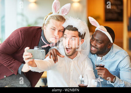 Friends celebrate bachelorette party and make a funny selfie together in a bar - Stock Image