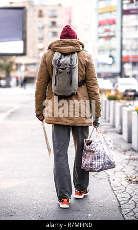 A rear view of homeless beggar man with backpack walking outdoors in city, holding bag. - Stock Image