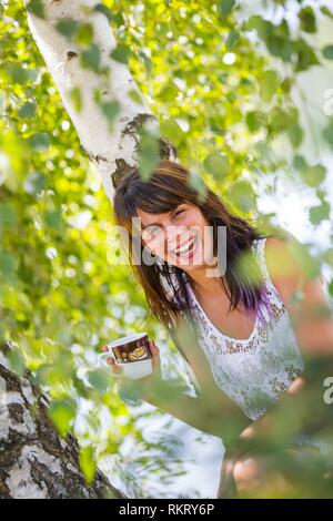 Attractive teenager girl is drinking coffee in nature looking at camera laughing extreme happy and smiling giggle giggling expressive expression - Stock Image