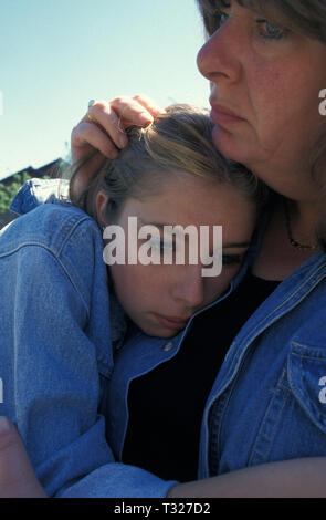 woman cradling anxious teenage girl against her chest - Stock Image