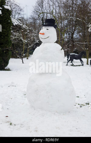 Snowman with black hat outdoors. - Stock Image