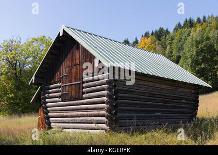 Small wooden rural house in the mountains on a sunny day in the summertime - Stock Image