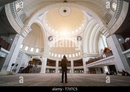 Young man traveler with backpack walking to Wilayah Persekutuan mosque in Kuala Lumpur, Malaysia. - Stock Image
