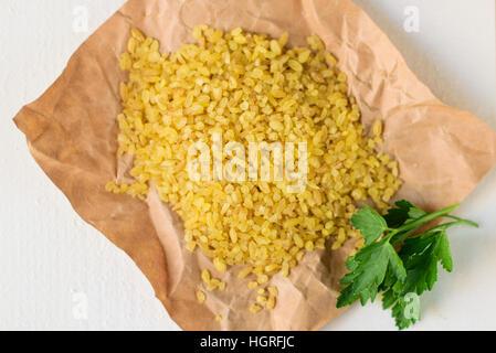 Bulgur wheat on wooden background - Stock Image