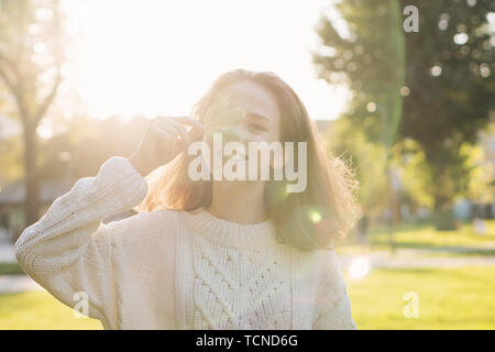 Portrait of European charming teen girl with a maple leaf in hands. She poses in rays of sunset and sun glare. Hides his face behind leaf of tree - Stock Image