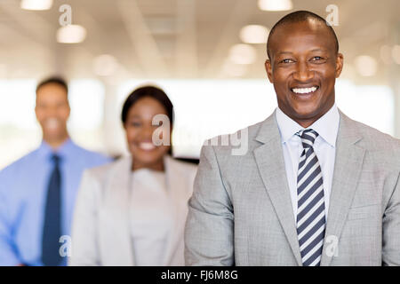 handsome African businessman standing in front of colleagues - Stock Image