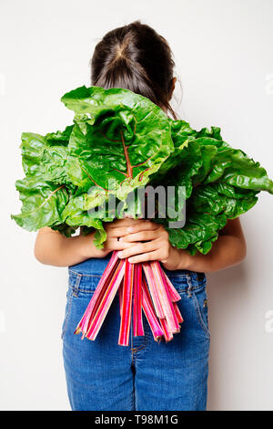 Little girl holding a bunch of fresh rainbow chard and hiding face behind the leaves as if I was praying or smelling - Stock Image