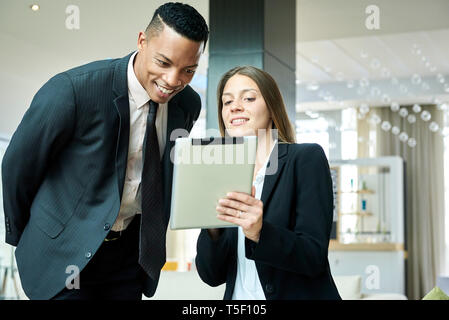 Business people using a digital tablet in hotel lobby - Stock Image