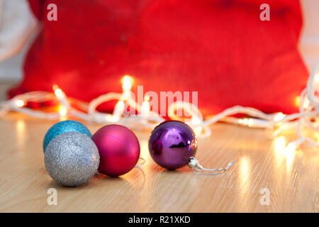 Purple, blue, silver and pink ornaments on the floor beside a red santa sack and christmas lights - Stock Image