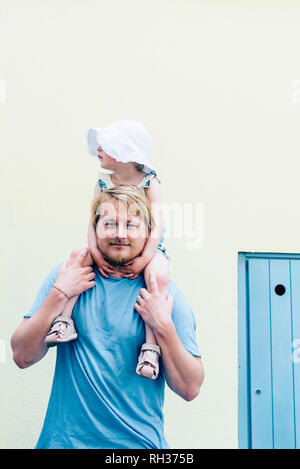 Father carrying daughter - Stock Image