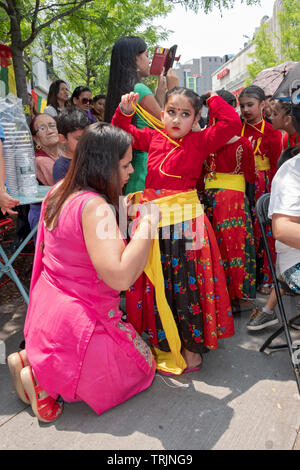 A Sherpa Buddhist mother adjusts her daughter's costume at a celebration of the anniversary of the first successful climb of Mt. Everest. In Queens NY - Stock Image
