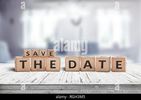 Save the date memo sign on a wooden table in a cozy bright room - Stock Image